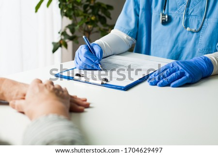 General Practitioner completing patient examination in doctor's office,filling out medical card form,diagnostic consultation & prevention of women's diseases,medical service,healthy lifestyle concept