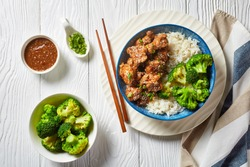 General Tso's Chicken crispy Chinese chicken bites in a bowl with rice and steamed broccoli florets, horizontal view from above, flat lay