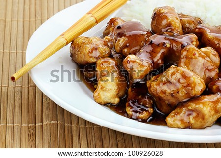 General Tso's Chicken served with white rice. Shallow depth of field.