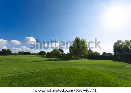 General view of a green golf course on a bright sunny day. Idyllic summer landscape with green trees and sunbeams in the sky. Sport, relax, recreation and leisure concept. - Shutterstock ID 650440771