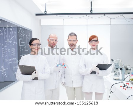 general-view of four co-workers in a chemistry lab around lab table with lab tools and colorful liquids and a blackboard on the background