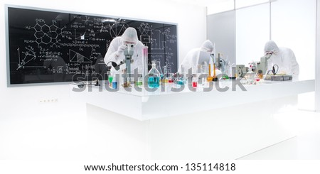 general-view of three people analysing  substances in a chemistry lab using colorful liquids and lab tools with a blackboard with chemical formulas on the background