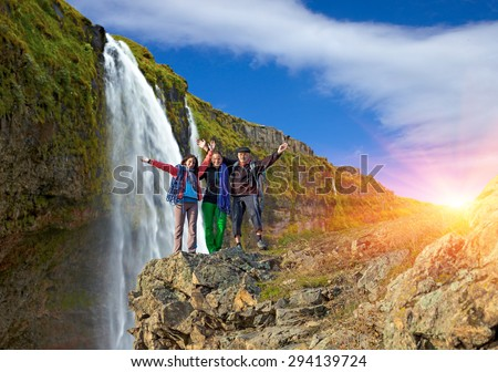 Generation family of hikers. Grandparent and granddaughters embracing three people group tourists staying on rock mountain cliff large waterfall background rainbow colored sun sunbeams blue sky