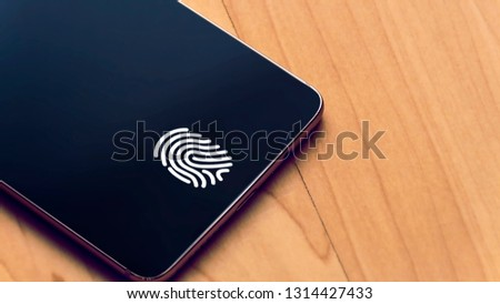 Generic Borderless (bezel-less) smartphone with a in-display fingerprint reader (Phone with full screen and a fingerprint icon) with warm wood background