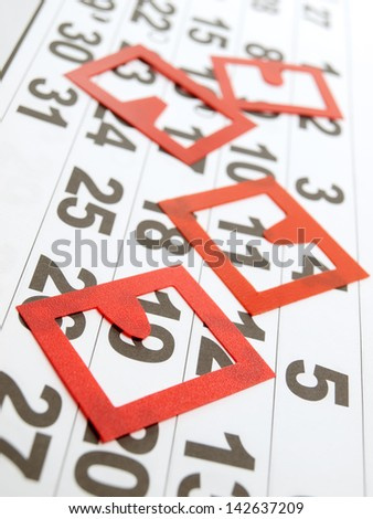 Generic calendar sheet with several red marking badges on it.