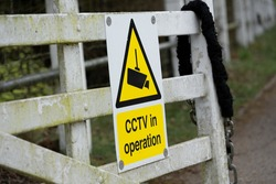 Generic CCTV Warning Sign seen attached to a garden gate in a rural location. The sign helps deter would-be criminals they are being recorded.