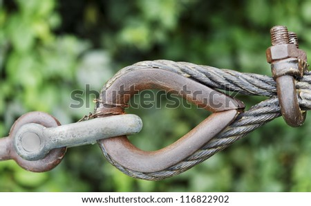 Generic eyelet and steel cables to guy ropes to strengthen a building structure, green leafy background, sunny day. Rusty metal which has been greased, angled concept shot