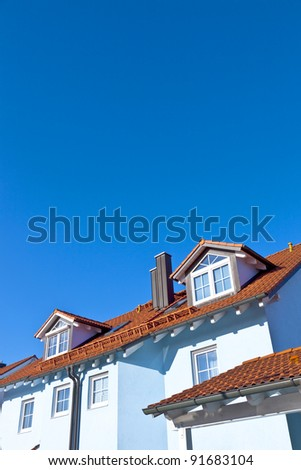 generic family home in suburban area with blue sky
