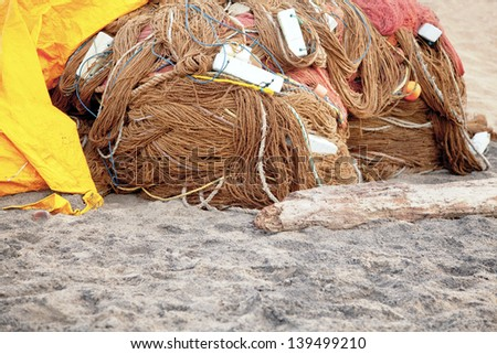 Generic horizontal color capture of a fish farming nets wrapped and stored overnight under a yellow tarpaulin on the sands at  Manaputta Beach, Pondicherry, Tamil Nadu, India
