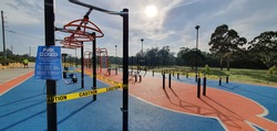 Generic imagery of the closed public park sport facilities in Sydney Australia due to Covid-19 pandemic with re danger and yellow caution tapes restricting access