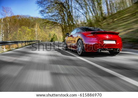 Generic red sports car driving fast on the open road