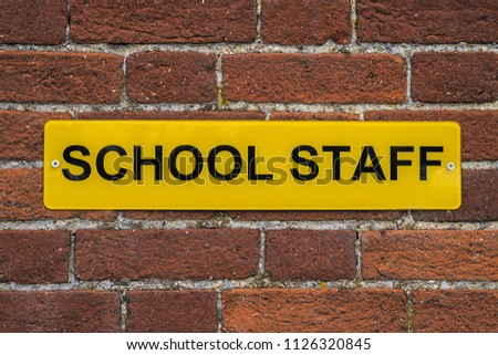 Generic SCHOOL STAFF yellow sign against a seamless brick wall. #1126320845