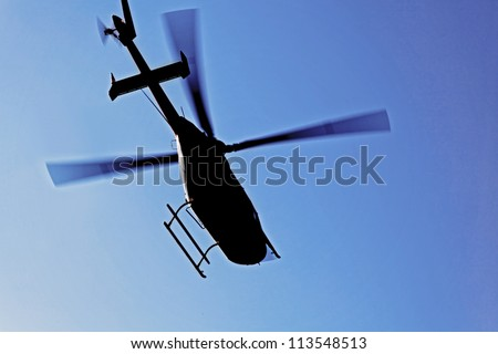 Generic silhouette of an helicopter caught  in flight against a clear blue sky. Actual location was Kashmir India but could have been taken anywhere on the globe