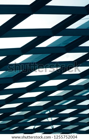 Generic structural glazing of an office or industrial building. Hi-tech abstract modern architecture or technology background.  Steel and glass roof / ceiling with rhombus elements. #1255752004