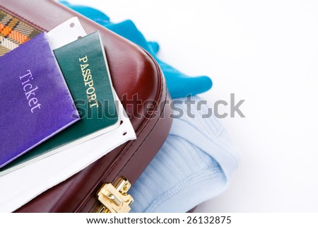 Generic ticket, passport and boarding pass on travel suitcase with some shirt shown from it.
