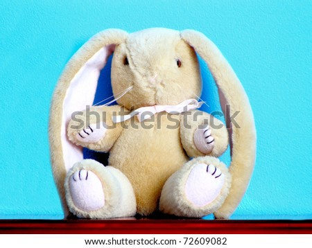 Generic toy Easter bunny sitting on a ledge against a bright blue wall background