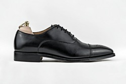 Generic unbranded high quality black brogue shoe shot from the side against a white background.