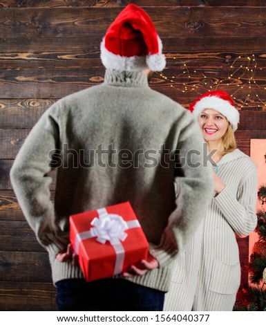 Generosity and kindness. Surprising his wife. Prepare surprise for darling. Winter surprise. Man carry gift box behind back. Woman smiling face santa. Christmas surprise concept. Giving and sharing.