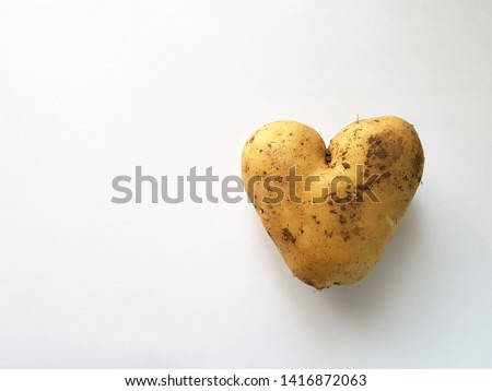Genetically modified food, heart shaped potato. Background with space for text. Production of modern farming and genetic engineering.