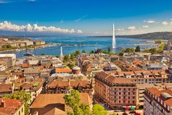 Geneva skyline cityscape, French-Swiss in Switzerland. Aerial view of Jet d'eau fountain, Lake Leman, bay and harbor from the bell tower of Saint-Pierre Cathedral. Sunny day blue sky.