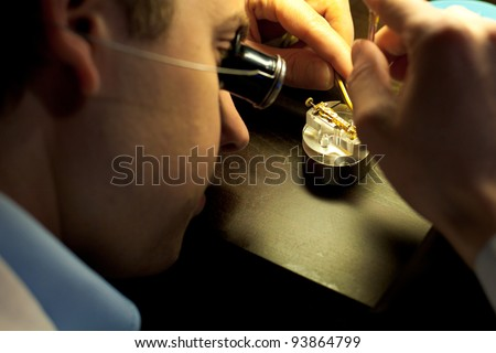 GENEVA, SWITZERLAND - NOV.13:  A Swiss watchmaker concentrates on assembling fine parts of a watch at The Watches Day, an exhibition of Swiss watchmakers November 13, 2011 in Geneva, Switzerland