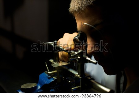 Geneva, Switzerland - November 13, 2011: A Swiss watchmaker grinds down a fine, crafted, tiny hand-made watch part during The Watches Day, an annual exhibition of Swiss watchmakers
