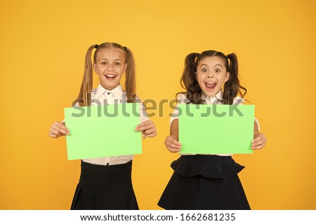 Genius advertising and marketing. Happy genius children holding blank paper sheets on yellow background. Genius girls smiling with empty posters. Genius idea, copy space.
