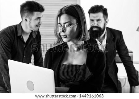 Genius and skillful. Genius woman working on laptop computer with people in office. Genius female worker using modern technology for business. Genius business lady wearing glasses with nerd look.