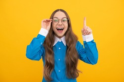 Genius idea. Girl genius with raised finger yellow background. Child prodigy in eyeglasses. Wunderkind. School education. September 1. Knowledge day. Happy childhood. Eureka.