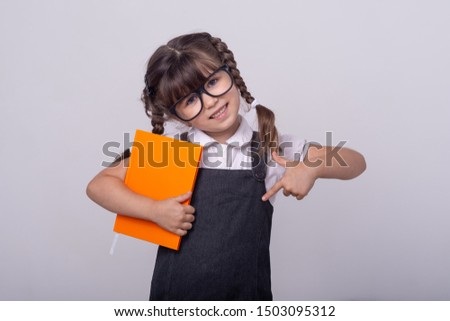 Genius little school child got a bright idea on grey background. Small girl holding book with genius ideas. Happy child genius or wunderkind.