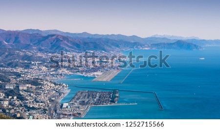 Genoa (Genova), Liguria, Italy: beautiful scenic aerial view of the city, port, dam, sea, Cristoforo Colombo airport runway, and Portofino promontory at sunset. Cityscape photography.