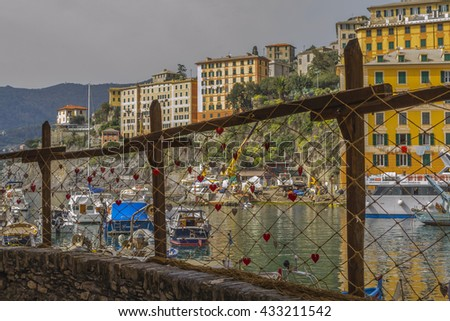 GENOA, LIGURIA, ITALY - April 3, 2016 : Panorama of the port of Camogli seen through a fishing net decorated with red paper hearts. #433211542