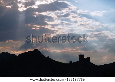 Genoese fortress silhouette with blue sky and clouds at sunset
