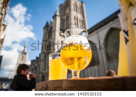 GENT, BELGIUM - AUGUST 29, 2010: Two belgian beers on a terrace table with a cathedral in the background #1450532153