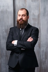 Gentelman fashion and style. Handsome young bearded man at suit and tie.