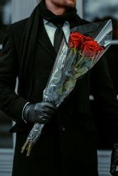 Gentelman holding in hands red roses