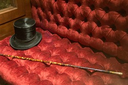gentelman vintage style black hat and cane elegant classic man accesories on red furniture couch