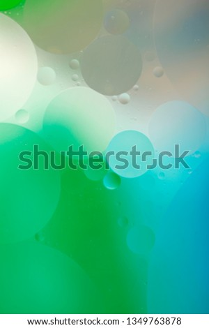 Gentle abstract blurred background. The texture of the liquid with circles and bubbles of green, blue and gray colors of different sizes. Cropped shot, macro, vertical, nobody, free space for text. #1349763878
