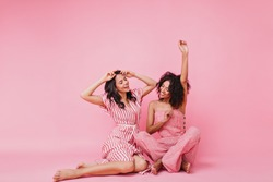 gentle and lovely girls with black curly hair, in pink pajamas having fun and raising their hands, dancing in front of camera