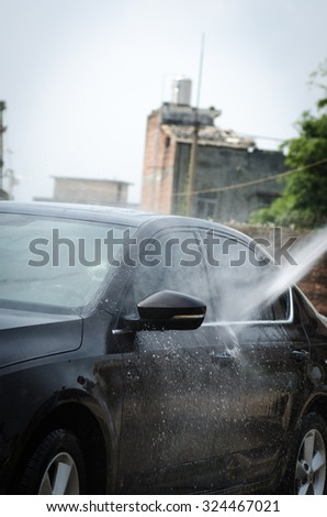Gentle car washing. Modern compact car covered by water.