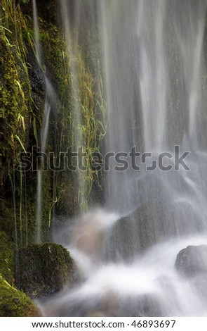 Gentle cascade of water over moss and rocks
