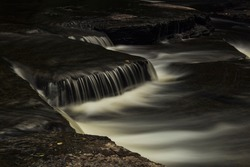 Gentle cascading waterfalls in and around Newburgh Ontario featuring lush foliage and ethereal long exposures of water over rocks.