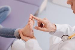 Gentle competent rheumatologist running diagnostic procedure