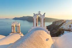 Gentle evening -  Romantic sunset sundown on famous Santorini island resort. Arch with a bell, white houses and romantic sundown sky in Oia at sunset, island Santorini, Greece, Europe