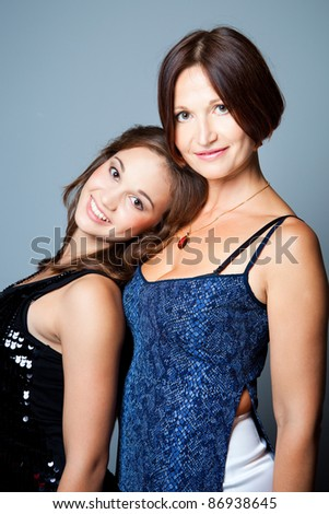 Gentle family relations of elegant mum with beautiful young daughter on blue background