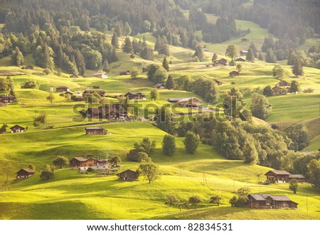 Gentle green hills of alpine village - stock photo