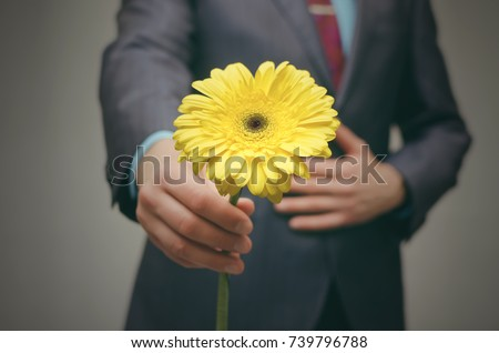 Gentle Man in suit gives yellow gerbera flower to someone. Meeting. Date. Rendezvous. Valentine day. #739796788