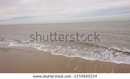 Gentle Pictures of the sea, The waves gently coming in, foaming and washing up all kinds of material.  #1259660254