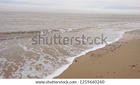 Gentle Pictures of the sea, The waves gently coming in, foaming and washing up all kinds of material.  #1259660260