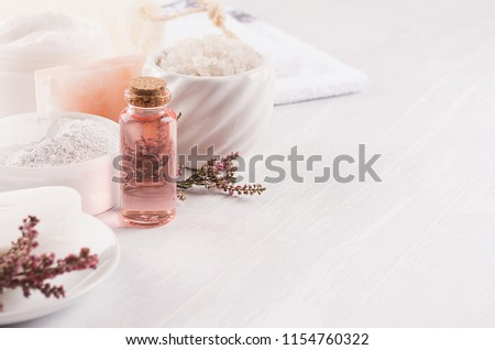 Gentle pink cosmetics oil, small flowers and white soap, cream, clay, towel closeup on white wooden background, copy space. #1154760322